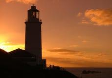 在日出的灯塔剪影 库存照片