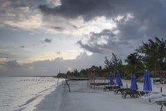 在日出的热带海滩与阴云密布、太阳床和蓝色太阳树荫 免版税图库摄影