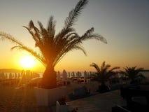 在日出的热带海滩与海滩睡椅和伞 免版税图库摄影