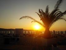 在日出的热带海滩与海滩睡椅和伞 免版税库存照片