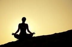 在日出的瑜伽姿势 免版税图库摄影