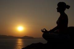 在日出的瑜伽姿势 免版税库存图片