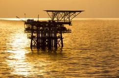 在日出的石油平台 库存照片