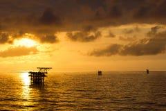 在日出的石油平台 免版税库存图片