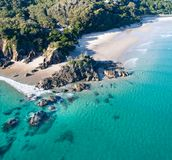 在日出的空中射击在海洋和白色沙滩与享受夏天的游泳者和冲浪者 免版税库存图片