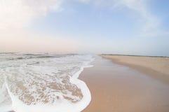 在日出的空的海滩与棕色沙子和多云天空 免版税库存图片