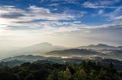在日出的薄雾山 库存图片