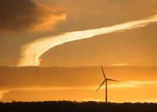 在日出的风轮机剪影 库存图片