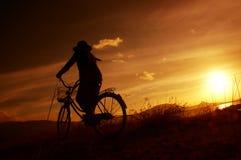 在日出的骑马自行车 库存照片