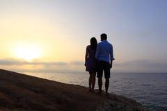 在日出的年轻夫妇剪影 免版税库存照片