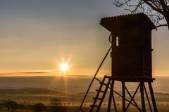 在日出的deerstand与背后照明 免版税库存照片