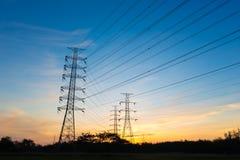 在日出背景的剪影高压电定向塔 免版税图库摄影