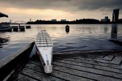 在日出背景的湖边附近停住的空的龙小船 免版税库存照片