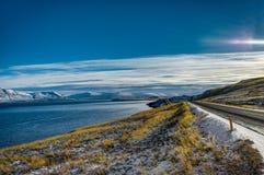 在日出金黄小时,有冰岛风景的空的街道 图库摄影