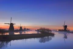 在日出,小孩堤防,荷兰的风车 库存图片