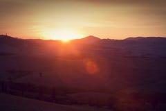 在日出,意大利的托斯卡纳风景 托斯坎小山,太阳火光 免版税库存照片
