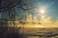 在日出-早晨在用冬天雪和冰盖的冬天河的冬天薄雾的冬天风景 免版税库存照片