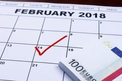 在日历和金钱14日标记的2月留出为礼物 库存照片