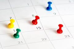 在日历栅格的多个颜色别针 免版税库存照片