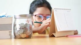 在日历的亚洲小女孩文字与在桌隐喻挽救金钱概念的玻璃瓶子 股票录像