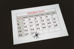 在日历的人为蜘蛛在黑背景 库存照片