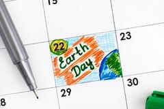 在日历的提示世界地球日与绿色笔 免版税库存照片