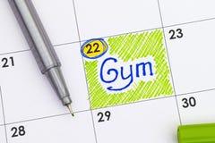 在日历的提示健身房与笔 库存照片