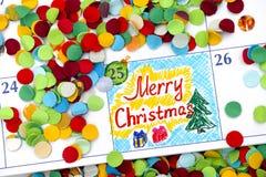在日历的提示圣诞快乐与五彩纸屑 免版税库存照片