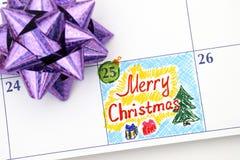 在日历的提示圣诞快乐与弓 免版税库存照片