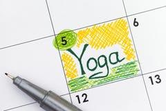 在日历的提示瑜伽与笔 免版税图库摄影