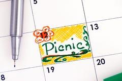 在日历的提示野餐与绿色笔 免版税库存照片