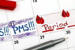 在日历的提示PMS和期间与红色笔 免版税图库摄影