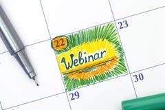 在日历的提示Webinar与笔 免版税库存图片
