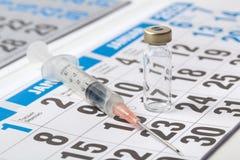 在日历的注射器和疫苗小瓶 库存图片