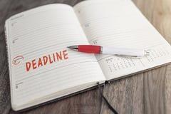 在日历的红色标记的工程截止期限日期在桌上 库存照片