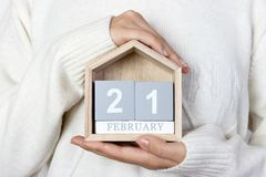 在日历的2月21日 女孩拿着一本木日历 世界母语日,国际旅游指南 图库摄影
