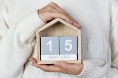 在日历的1月15日 女孩拿着一本木日历 世界雪天,世界宗教天 免版税库存图片