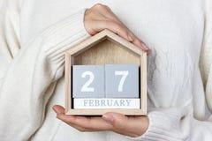 在日历的2月27日 女孩拿着一本木日历 国际北极熊天,起点借 库存照片