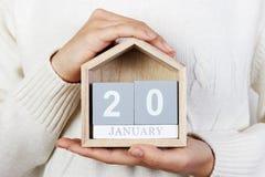 在日历的1月20日 女孩拿着一本木日历 就职典礼日 免版税图库摄影