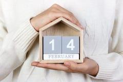 在日历的2月14日 女孩拿着一本木日历 情人节,国际天书礼物,天 免版税库存照片