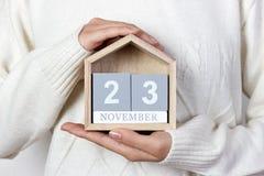 在日历的11月23日 女孩拿着一本木日历 感恩日 库存照片