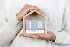 在日历的1月19日 女孩拿着一本木日历 罗伯特李的生日 免版税库存照片