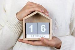 在日历的1月16日 女孩拿着一本木日历 Beatles天 免版税库存图片
