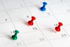 在日历的绿色红色蓝色别针 免版税库存照片