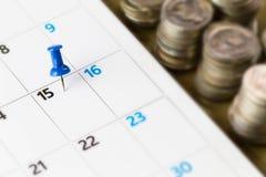 在日历的Pin在第15与被弄脏的硬币的月 免版税库存图片