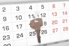 在日历背景的一把房子钥匙 免版税库存照片