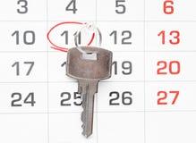 在日历背景的一把房子钥匙 免版税图库摄影