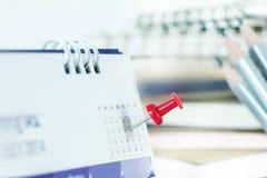 在日历页的红色图钉为提醒和被标记的重要前夕 免版税图库摄影