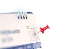 在日历页的红色图钉为提醒和被标记的重要前夕 免版税库存照片