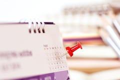 在日历页的红色图钉为提醒和被标记的重要前夕 图库摄影